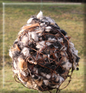 Outdoor ball ornament filled with alpaca fleece for bird nesting material.
